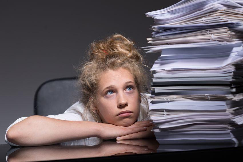 Chica mirando pila de papeles como ejemplo de cómo evitar que te agobie tu trabajo