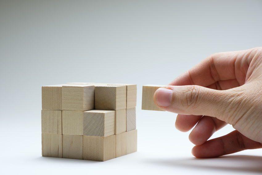 Mano añadiendo última pieza a un cubo como ejemplo de en lugar de perfección busca la finalización