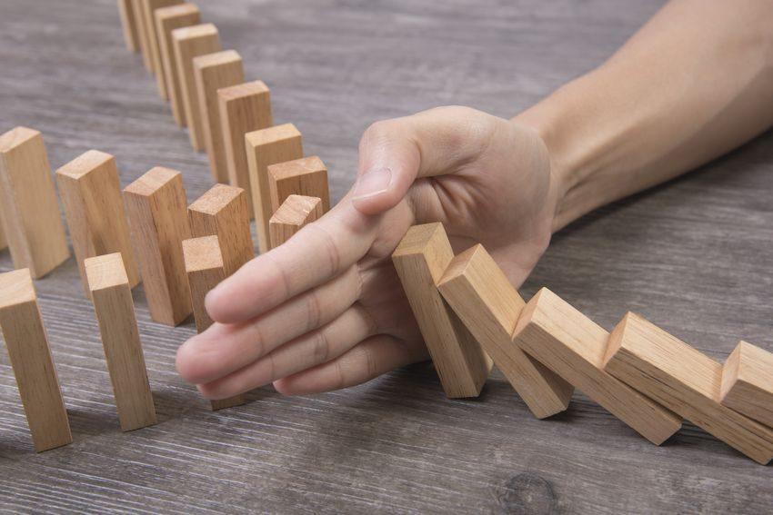 Mano deteniendo caída fichas de dominó como ejemplo de cómo hacer control de daños con GTD®