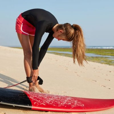 Chica surfista colocando agarre en el tobillo como ejemplo de prever