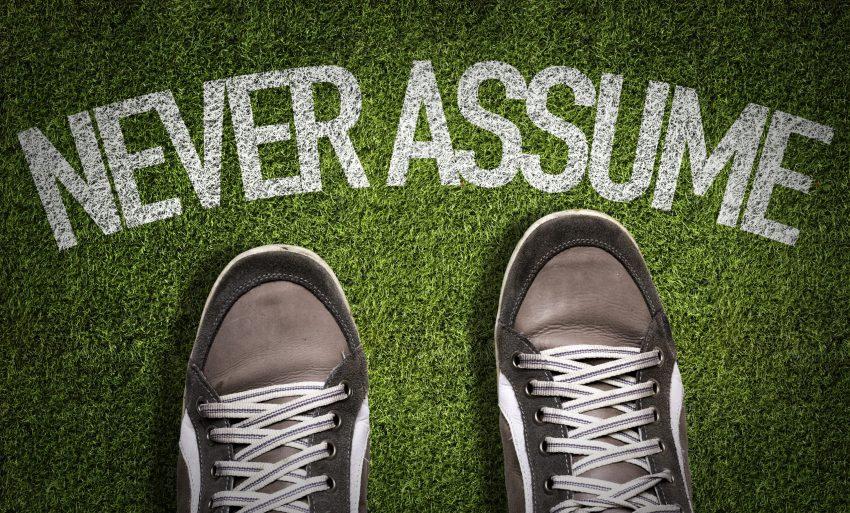 Zapatillas y texto «never assume» como ejemplo de efectividad es prever en lugar de suponer