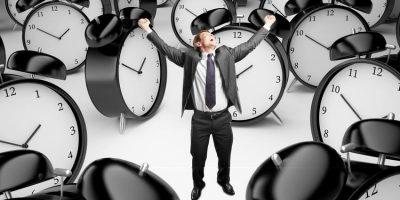 Hombre rodeado de despertadores como ejemplo de buenas y malas prácticas al usar alarmas